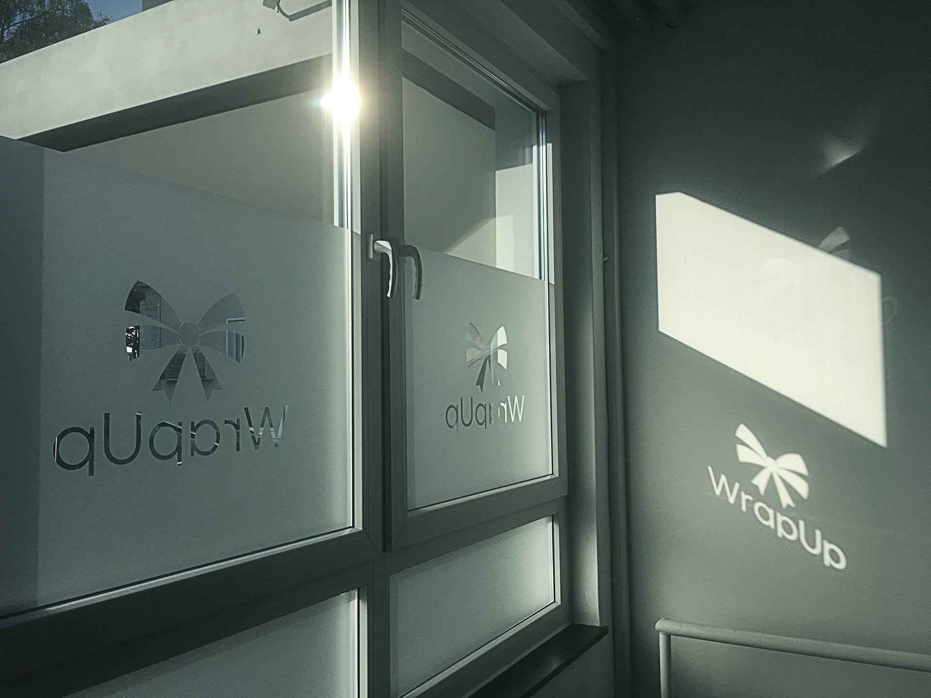 Window privacy protection with stamped out company logo, privacy protection foils and glass decoration foils lettering from anplakt